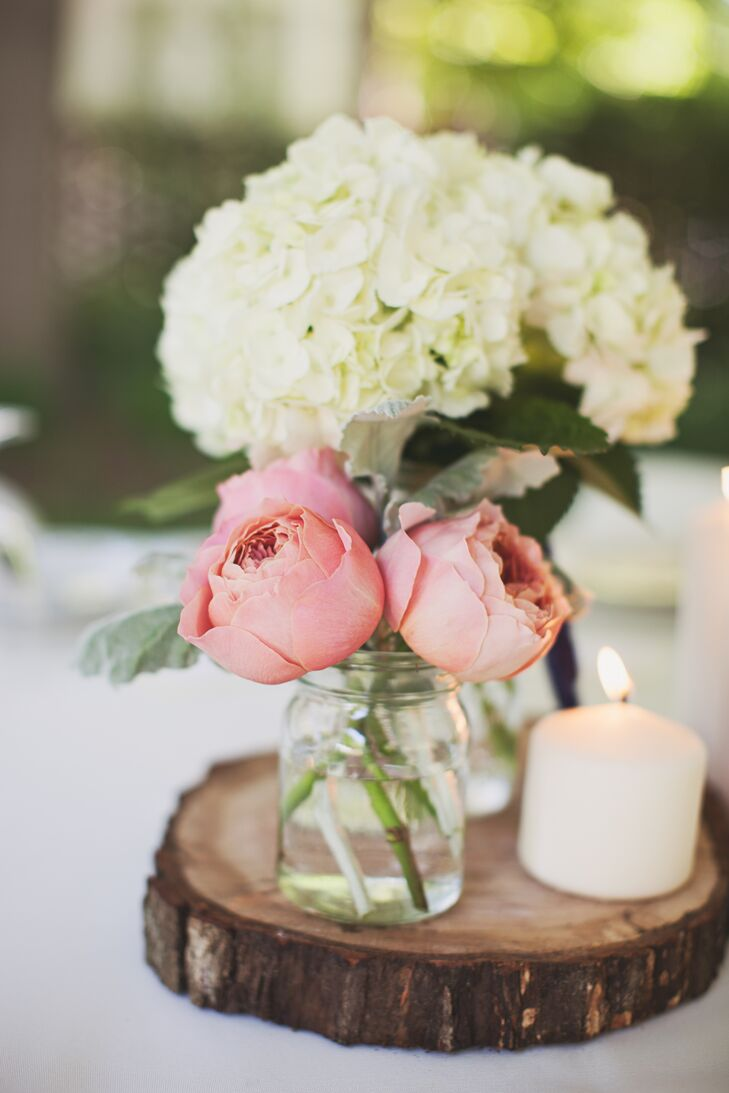 The reception tables were decorated with pink peonies, white hydrangeas and white pillar candles on top of unfinished wooden slabs hand cut by Alex.