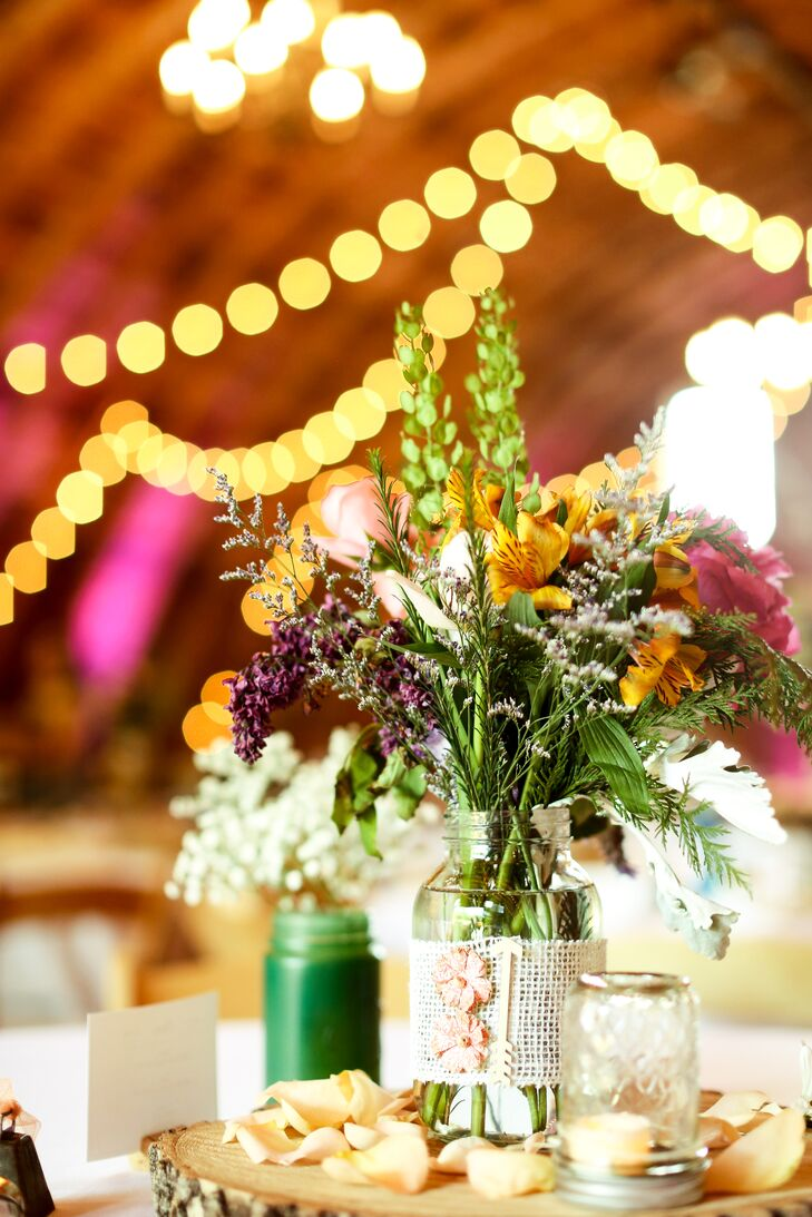 The reception tables were topped with mason jars filled with yellow alstromeria and wildflowers. Burlap, unfinished wooden rounds and rose petals brought the shabby-chic look to life.
