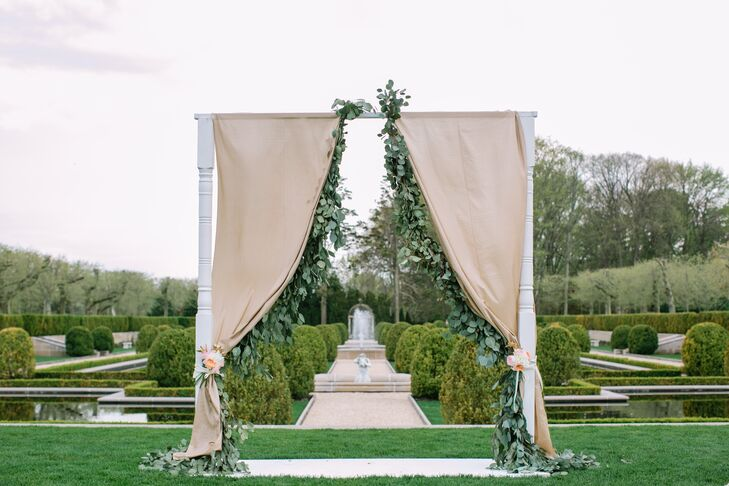 Cheeky Details created a custom wedding ceremony arch that was covered in soft champagne dupioni fabric and draped silver dollar eucalyptus garland that we made from each side.