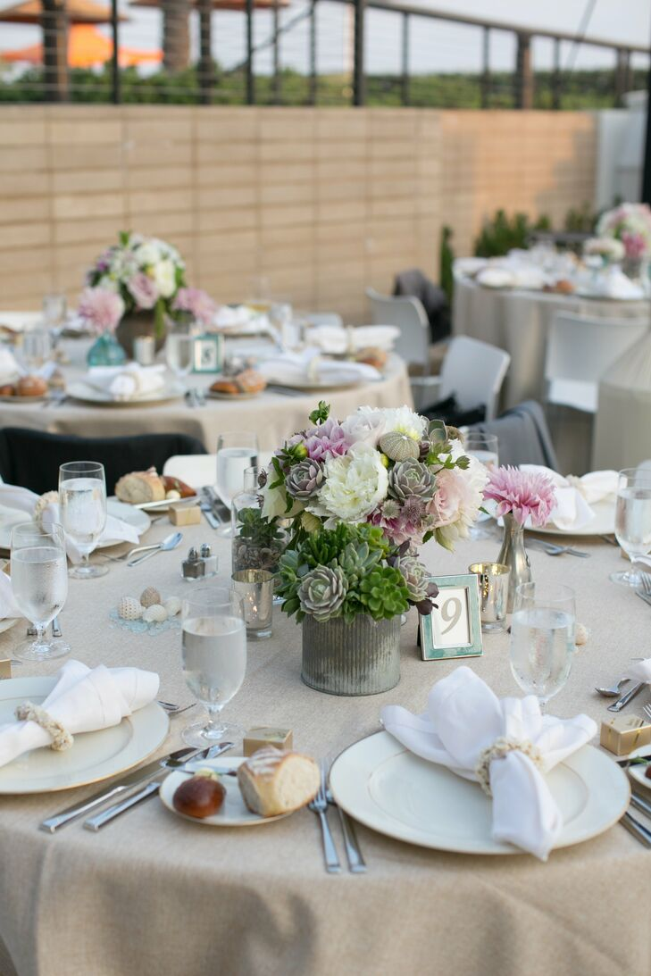 Weathered cans and mercury glass vases held an assortment of succulents, peonies, roses, dahlias and sea shells.