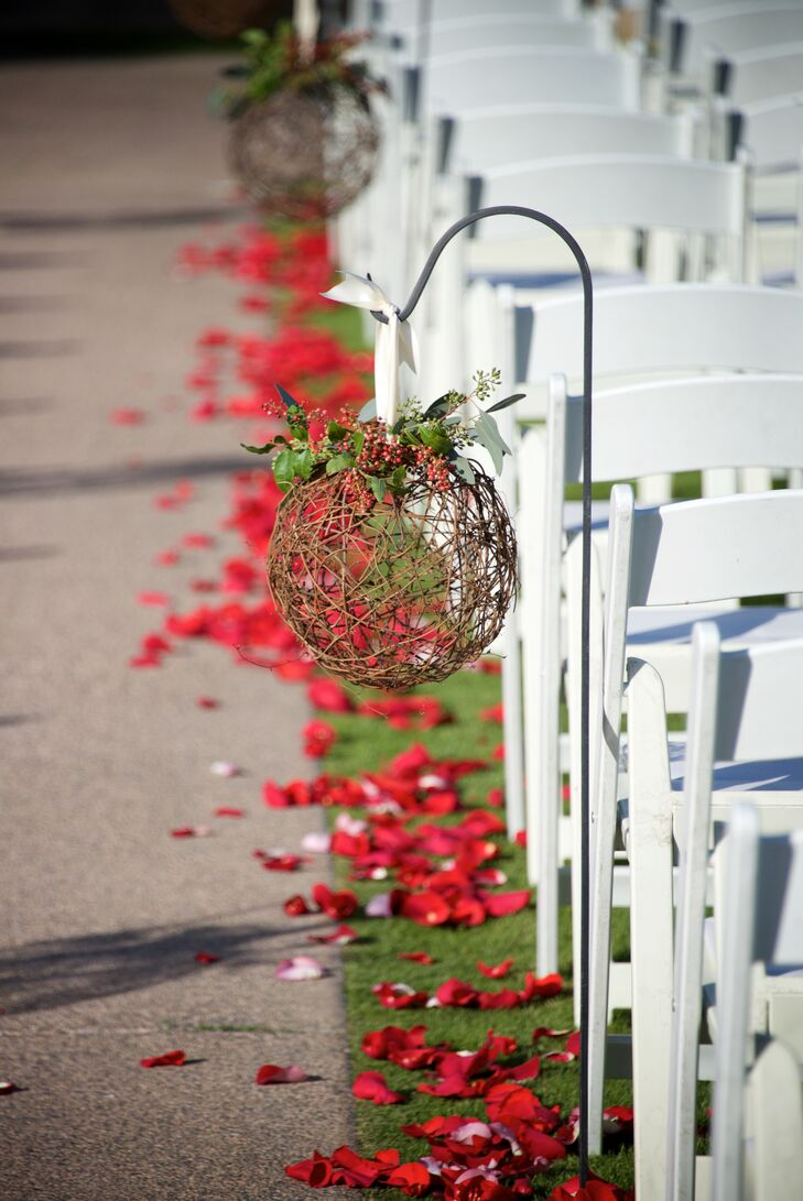 The aisle was decorated with red rose petals and twig spheres topped with red berries to create a holiday atmosphere.