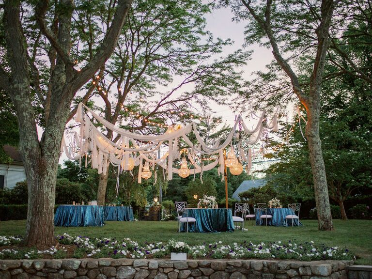 White drapes hanging from trees at backyard summer wedding