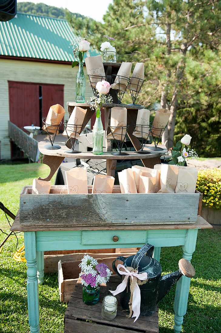 As guests arrived at Mary and Sam's wedding ceremony, they found a popcorn machine and paper bags stamped with Mary and Sam's initials for filling with the popcorn.