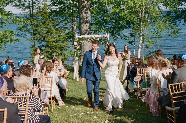 """""""The ocean did most of the decorating for our ceremony,"""" Jamie says. """"We kept our decor very simple, because our location was truly the star."""" For their Jewish ceremony, a chuppah was embellished with greenery, peonies and garden roses, and petals were scattered down the aisle."""