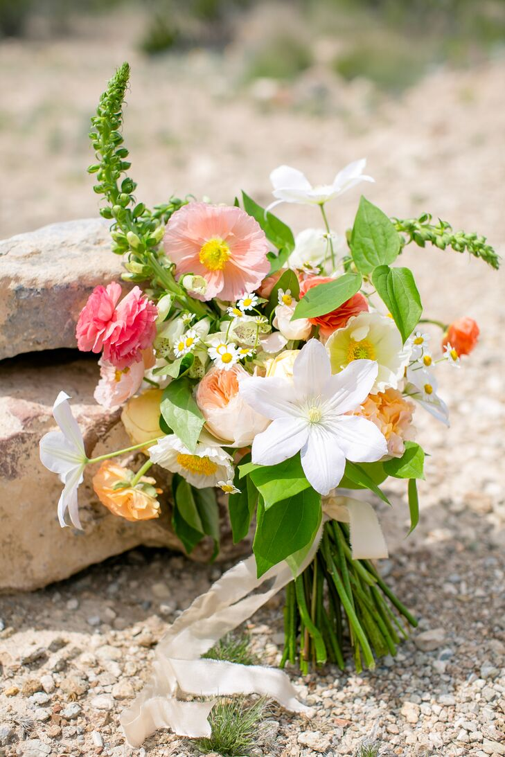 The peach, pink and white hues in Valerie's bouquet were inspired by the sunsets of Big Bend National Park in Texas. Garden roses, spray roses, ranunculus, poppies, foxglove, chamomile, and clematis composed the arrangement.
