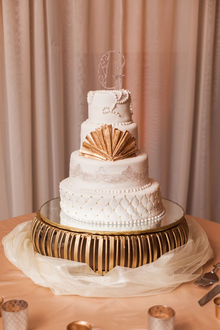 "Their wedding cake followed suit with a 1920s-style design. Every layer had a different look, including lace-inspired draping, pleating with gold Swiss dots and edible pearls. For the second tier, they even mimicked the gold base with a matching 3-D fan. A delicate ""G"" with scrollwork represented their last name as the topper."