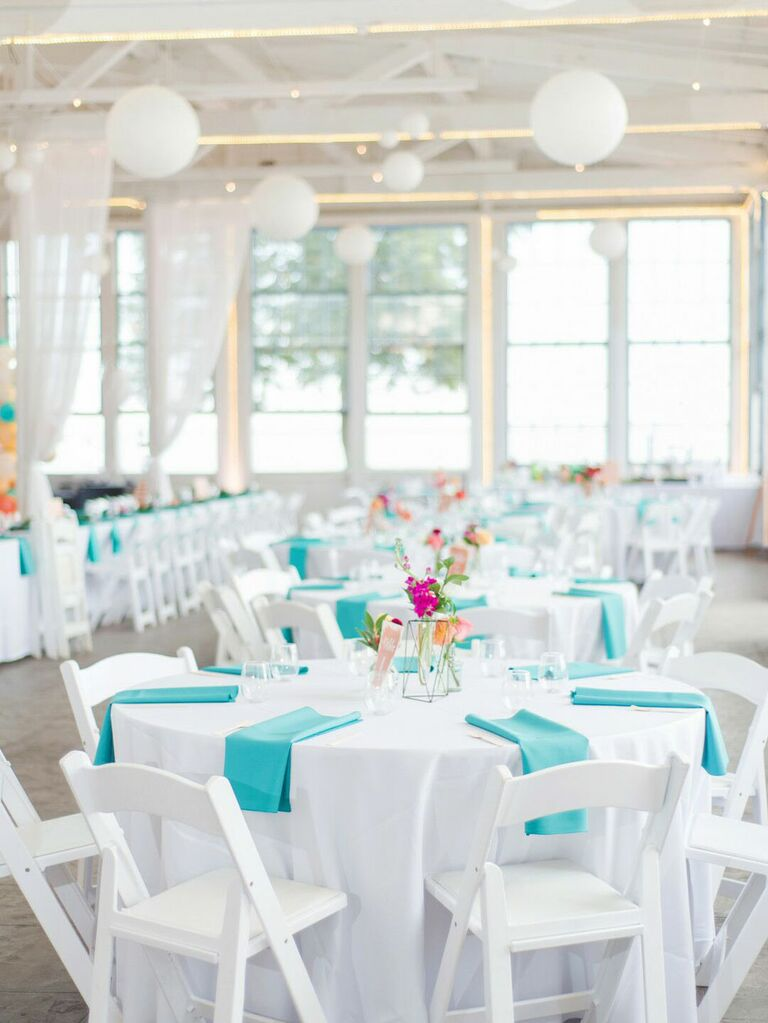 Summer wedding reception with white tables and chairs and teal linens