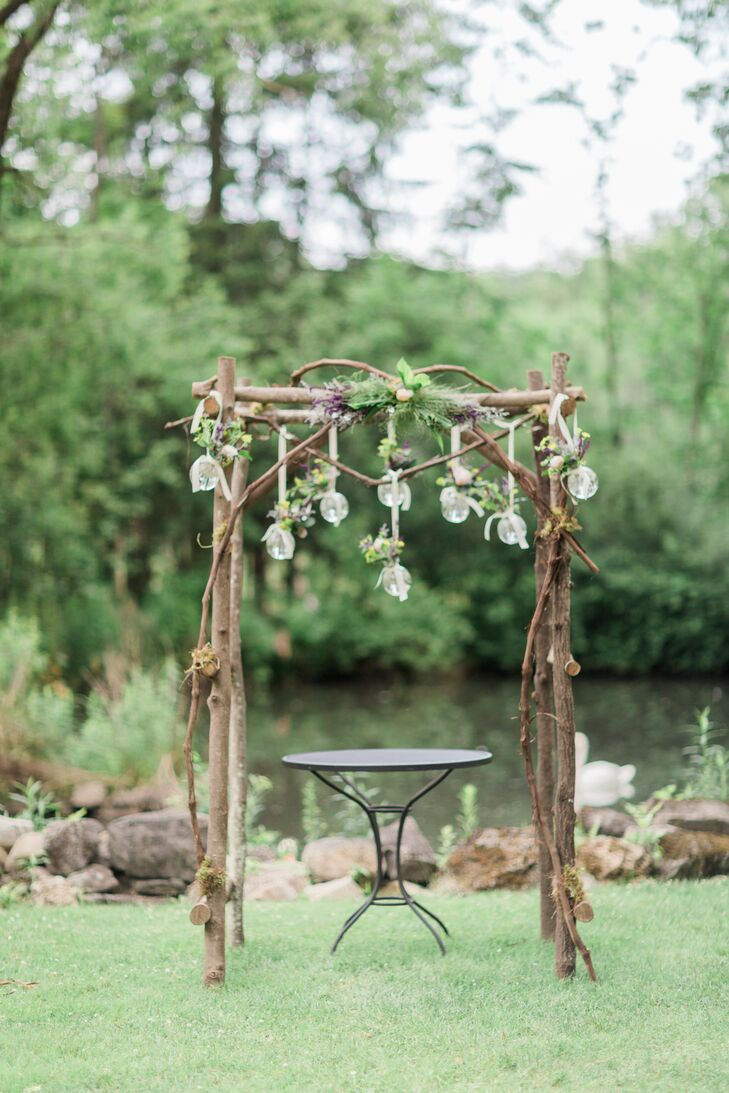Emily and Ben were married outdoors under a natural wooden arch by the pond at  Mansion Inn. Glass orbs filled with flowers hung from the arch.