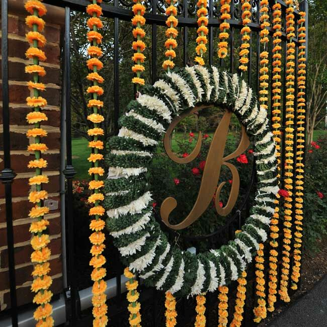 Garlands and a wreath of flowers decorated the gate to the groom's parents' home where the Sangeet was held.