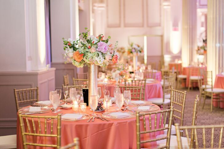 Dining tables were cloaked in cheery coral linens and topped with floral arrangements in tall gold trumpet vases. Other glitzy accents included beaded glass chargers, mirrored glass frames displaying table numbers and chaivari chairs.
