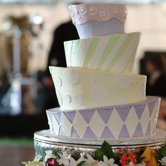 Doug designed the four-tiered Mad Hatter-style cake. He chose a pastel palette for the buttercream frosting of purple, yellow, green, and pink, which complemented the rich-colored tablecloths. The best part? The flavor was dark chocolate mousse.