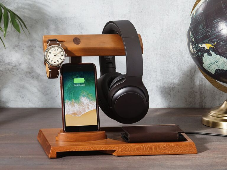 Wooden docking station holding headphones, watch, wallet and phone