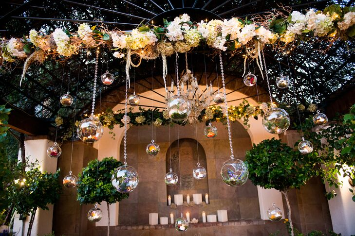 At the ceremony site, the couple filled glass globes with a variety of ranunculus, delphiniums and other flowers with moss and lights at the bottom, which twinkled softly during the reception.