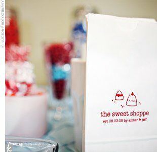 """In addition to wedding cake, guests indulged in a """"candy shop"""" table, which included rock candy, lollipops, licorice, bubble gum, chocolates, and other candy in the couple's signature aqua and red wedding colors.  The treats came with easy take-home bags, which had been custom-printed for the day."""