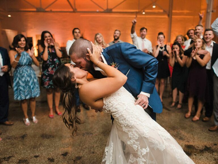 Bride and groom kissing during first dance at wedding reception