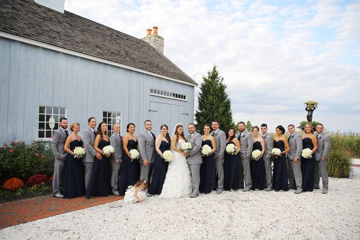 Each bridesmaid wore a traditional floor-length navy dress by Bill Levkoff with a sweetheart neckline and an updo hairstyle. They carried bouquets of white hydrangeas that paired nicely the bride's all-white arrangement .