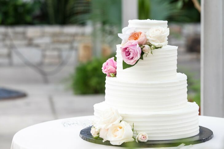 The four-tier white cake was decorated with fresh flowers.