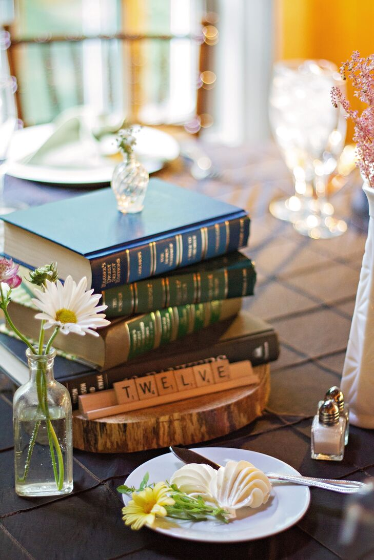 Centerpieces at the reception consisted of stacks of books on wood slabs with small vases of daisies. Table numbers were indicated with Scrabble tiles.