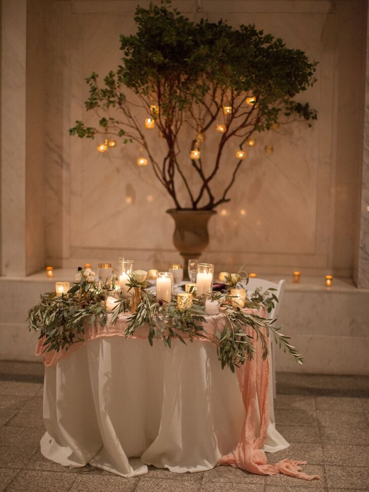 After the ceremony, Sydney and Dustin's sweetheart table was placed in front of the manzanita-branch-filled urn where they had exchanged vows. Their table was draped in blush fabric and embellished with romantic pillar candles and olive branches.