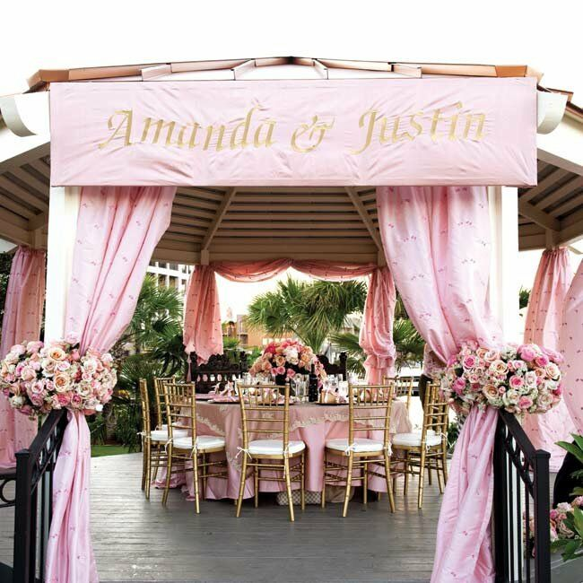 The head table got major VIP treatment: its own gazebo overlooking the lake. Flowy pink draping and a banner with the couple's names finished the look.