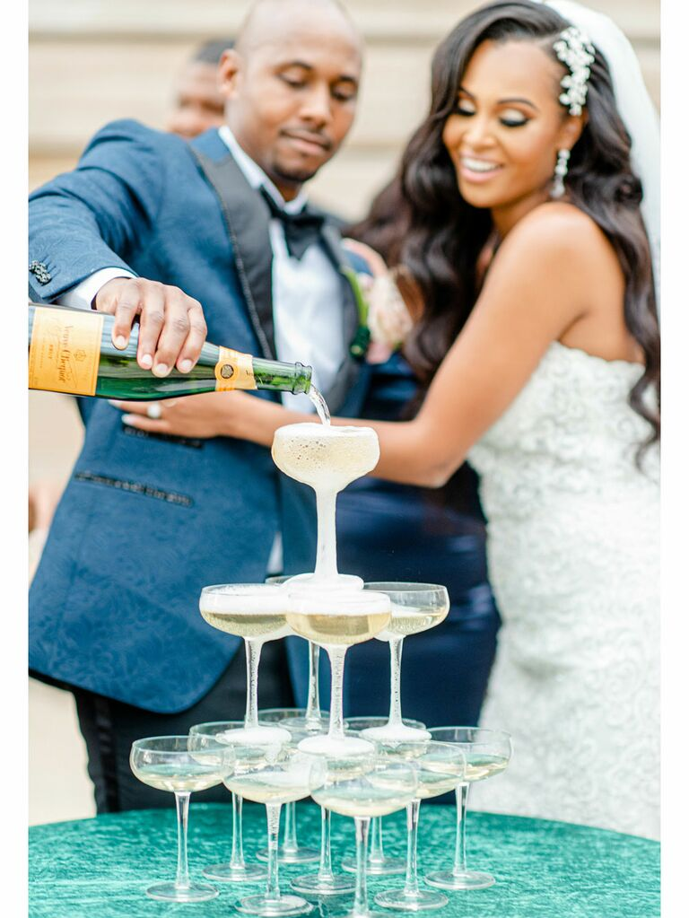 Bride and groom pouring champagne on art deco-style champagne tower