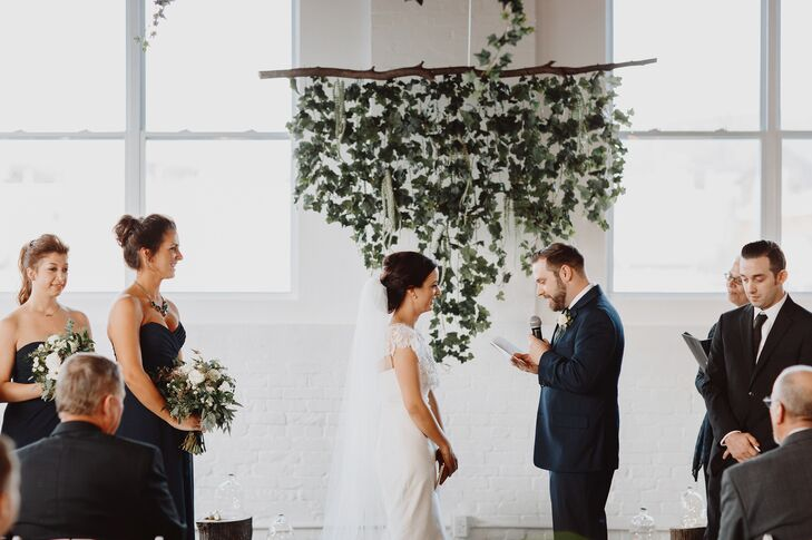 """With its natural wood floors, tall ceilings, whitewashed brick and wall-to-wall windows, Reading Art Works in Reading, Pennsylvania, offered a raw space for Shannon and Jason to make their own. Wanting to highlight the setting rather than detract from it, the couple kept the decor for the ceremony simple, adding only a few wooden logs, fairy lights and a hanging installation with cascading vines and flowers to the space to create a whimsical, rustic backdrop against which to say their """"I dos."""""""