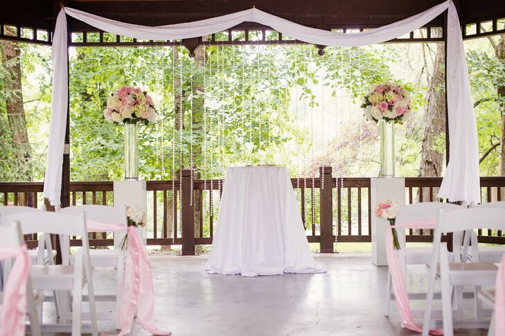 Kylie and Travis decorated their wedding alter with beaded crystal strings, white drapery and large blush and white floral arrangements.