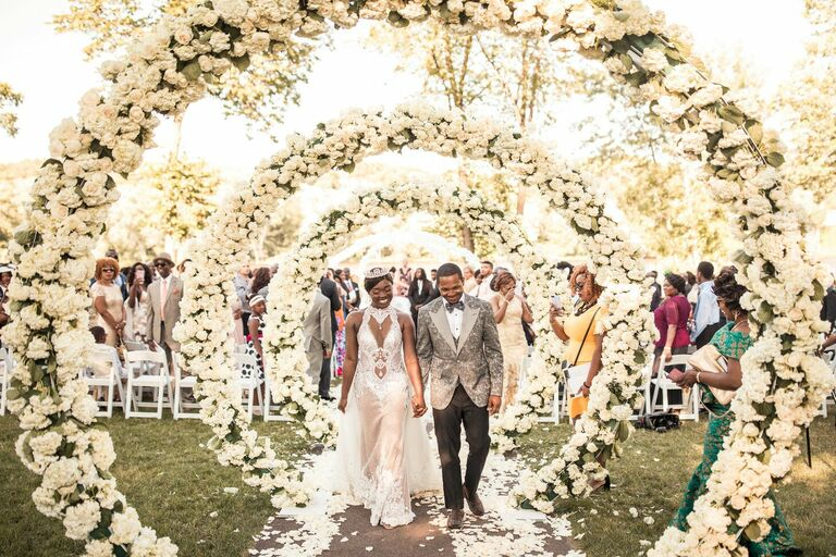 Couple exiting wedding ceremony under white floral arches