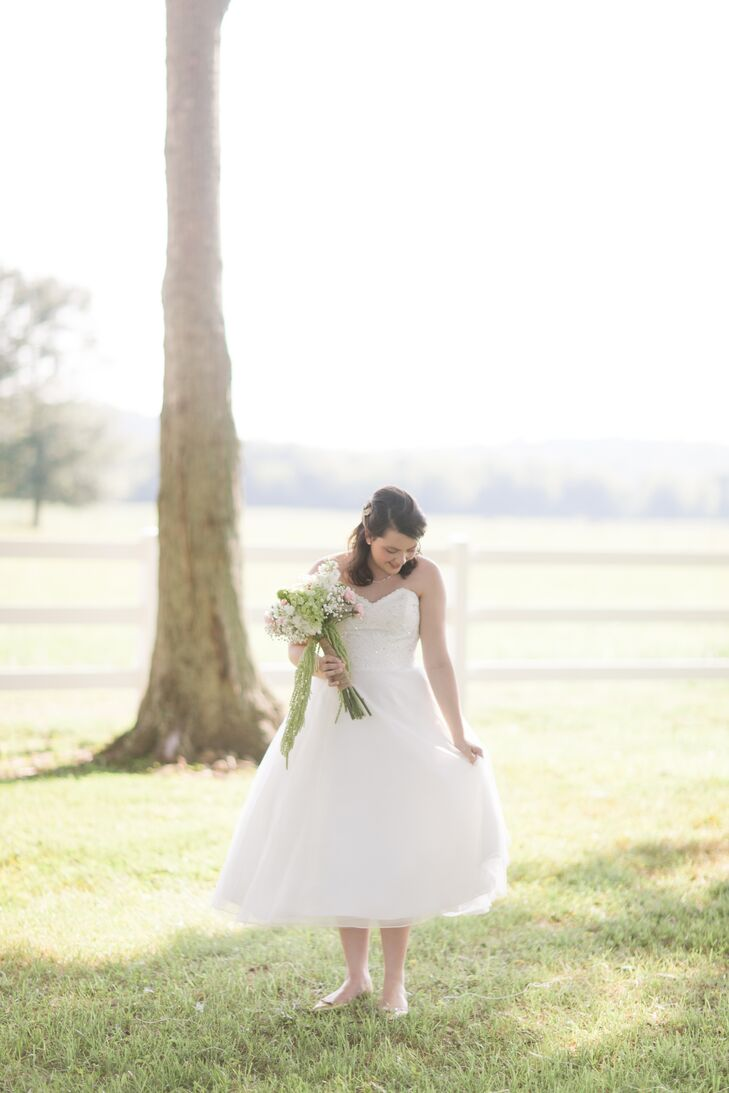 """Because Alix and George started planning their wedding only after Alix had graduated from college, it left only two months for her to find a wedding dress. Luckily, she quickly found the perfect fit — a sweet tea length dress by Mori Lee with a lace bodice and sweetheart neckline. """"I had just explained my ideal dress to my mom when we passed the bridal shop where she bought her own wedding dress,"""" says Alix. """"I saw a dress in the window and said 'Oh my stars you've got to turn around — that's my dress,' and it was. My dress was in same window my moms had been in 21 years ago."""""""