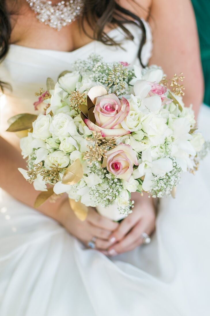 "Erin carried a bouquet of white hydrangeas, baby's breath, pink-tipped roses and gold leaves. ""We wanted to keep the flowers earthy and natural,"" she says."