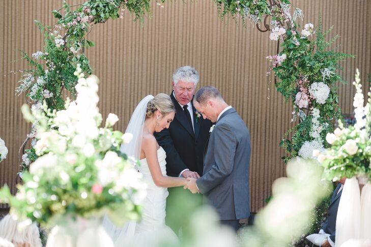 "Before kicking off a fun-filled night of dinner and dancing, Brianna and Barrett exchanged vows in an outdoor ceremony overlooking the Lakeridge Country Club golf course. The pair said their ""I do's"" standing under an ornate wedding arch draped in lush greenery and full pink flowers."