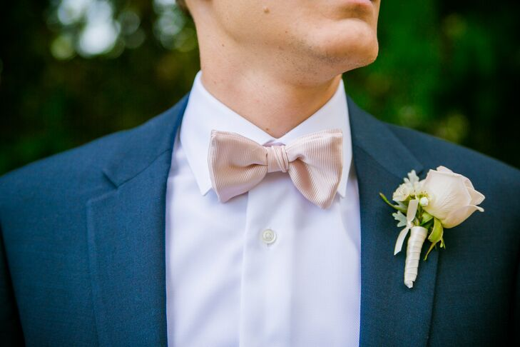 The groomsmen sported navy blue suits paired with a blush bow tie that matched the wedding's overall palette. Their blush-colored boutonnieres incorporated the same flowers that were used in all the bouquets and flower arrangements.