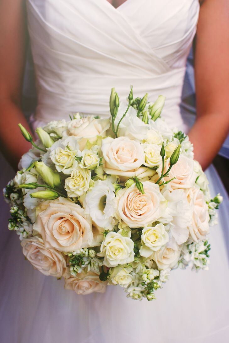 Steph held an elegant round bouquet filled with a classic arrangement of flowers: blush and white roses mixed with white lilies. The flowers went along with her traditional white dress as she walked down the aisle.