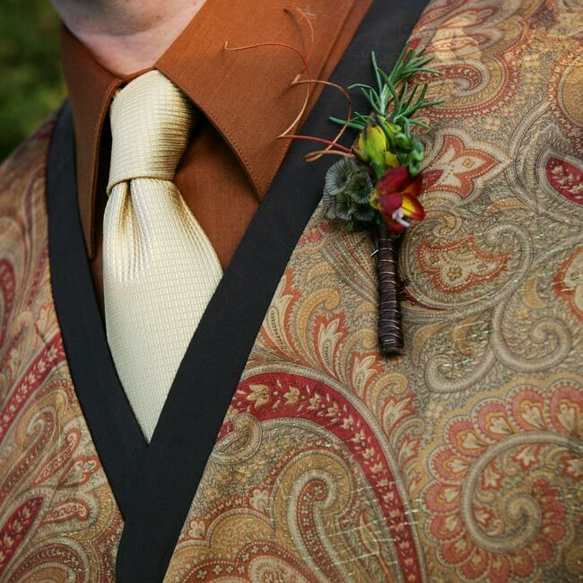 """""""We found this fantastic orange paisley material and decided this is what we would use to pull the entire bridal party together,"""" Tatiana explains. """"My mom made ties for our officiant and the best man, cloth flowers for the girls, and Chris' vest."""" Orange not only fit the fall theme; it is also the groom's favorite color, so it worked perfectly. The boutonnieres were also a mix of fresh and dried flowers. """"Some of the boutonnieres had acorns, others had rosemary,"""" Chris says."""