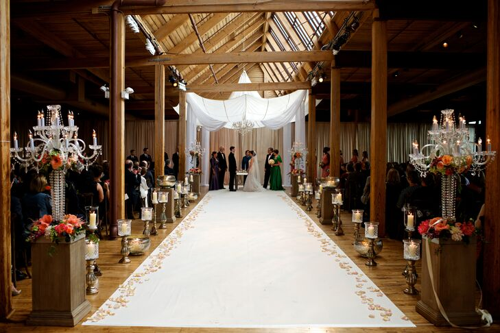 The skyline view and brick and wood surroundings in the Bridgeport Art Center Skyline Loft ceremony location invited guests into the warm, romantic space. Candles and peach, pink and soft green flowers adorned the white linen aisle leading up to a huppah, repurposed from a 1920s parachute.