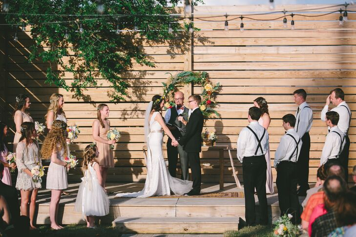 "Kenzie and Jon exchanged vows in an outdoor ceremony in the Guild's private urban garden. The sun began to set as the pair said their ""I dos"" on the simple stage, the warm, diffused light filling the lush, intimate space with undeniable ambiance. The decor was kept on the understated side, so as not to detract from the setting, with the couple adding only a few details—a rug, a side table, a few subtle floral arrangements—to the stage and altar for a hint of bohemian flair."