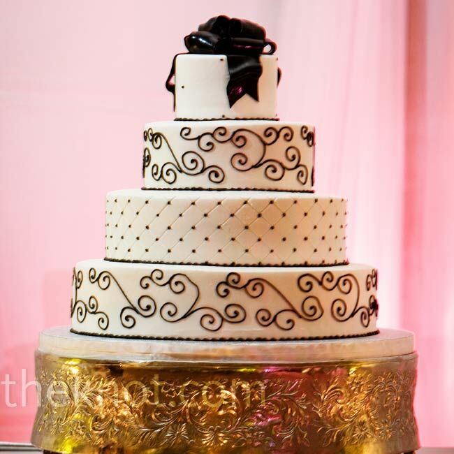 A scrollwork pattern and playful dots decorated alternating tiers on the cake. The dessert rested on a gold stand surrounded by petals and candles for a finished look.