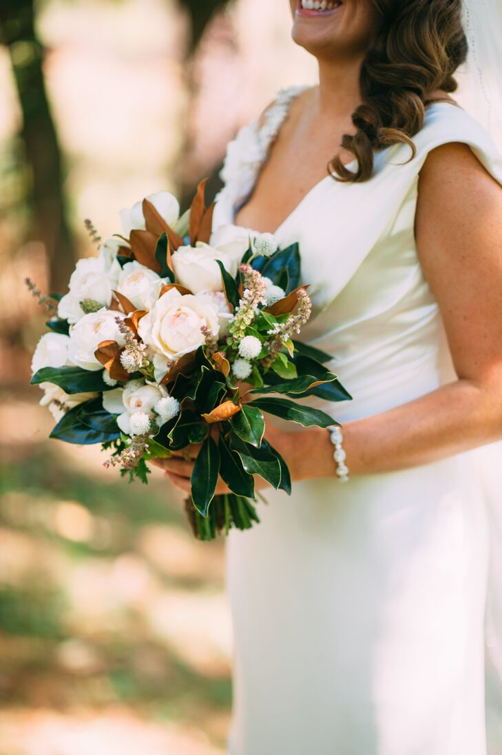 Since Molly's favorite flower, peonies, weren't in season during the time of her wedding, Andrea from LynnVale Studios helped her craft the perfect bouquet. She used ivory and blush roses that resembled peonies and paired them with leaves from Ryan's parents' magnolia tree, since Molly also loves magnolia. She also incorporated small, white dahlias into the bouquet as well as basil leaves, which had the arrangement smelling fresh all day.