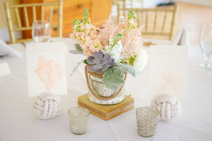"""""""From the start I had a vision in my head of a whimsical, ethereal and vintage feel mixed with nautical elements,"""" says Lindsey. Every table was set  to this notion with a low arrangement of succulents, pink and white delphiniums, dusty miller and pink astilbe inside a silver vase wrapped in rope. Wanting to take the nautical theme a step further, they also had table numbers made of knotted rope and chic seashell-inspired table names."""