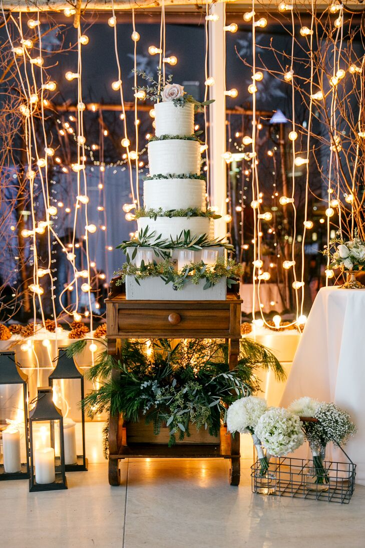 The vanilla buttercream wedding cake was flavored chocolate and almond. The white cake was decorated with eucalyptus leaves and displayed on a vintage table, which was decorated with greens. The table was flanked by candle lanterns and white floral arrangements and positioned in front of a curtain of string lights.