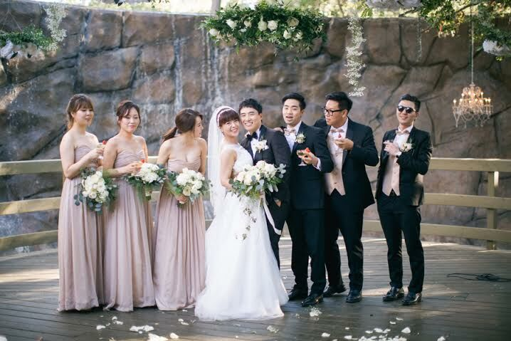 """The bridesmaids were wearing champagne-gold strapless dresses. They were gorgeous,"" Woo Jin says. These subtle warm gold tones fit well with the greenery-rich bouquets. The groomsmen sported traditional tuxedos and gold bow ties."