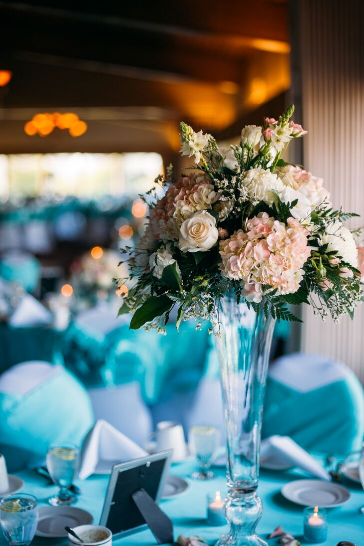 Romantic arrangements of roses, hydrangeas and ferns were displayed in tall glass vases for the centerpiece decor.