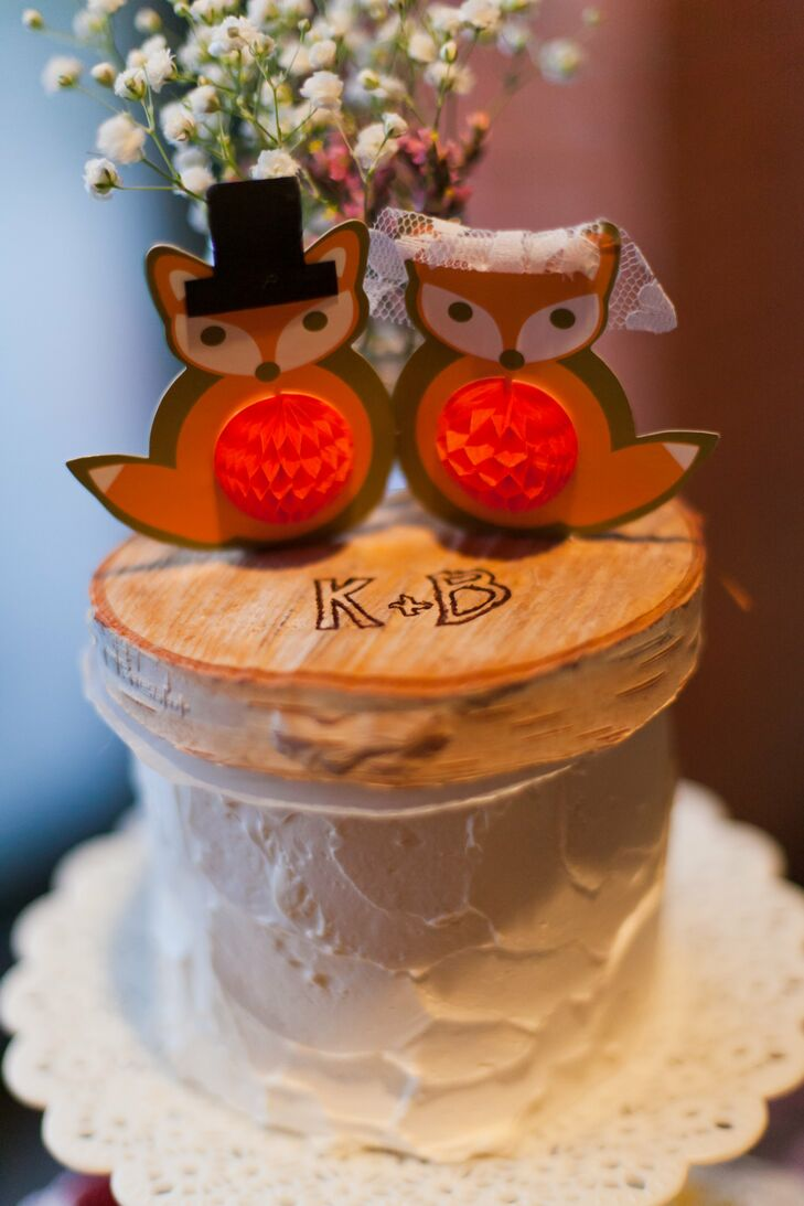 The adorable paper fox cake topper was displayed on top of a small wood slab with Kristen and Blake's initials etched into it. I love foxes, so the topper was a way to personalize the cake a little bit, says Kristen.