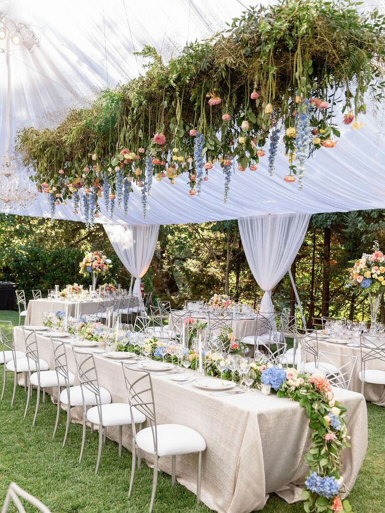 White wedding tent with suspended florals and greenery above reception tables