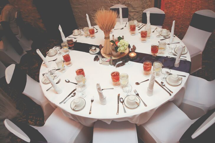 The reception tables were decorated with purple table runners topped with wooden round centerpieces that included dried wheat, white hydrangeas and pine cones to match the fall wedding.