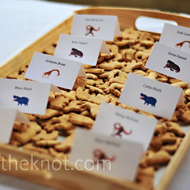 To play up their vintage zoo theme, Tara and Mike designed their escort cards with each guest's name and an animal image from children's author and illustrator Eric Carle. They displayed the cards in trays full of animal crackers.