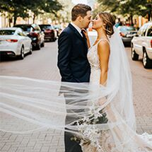 bride and groom about to kiss in middle of street
