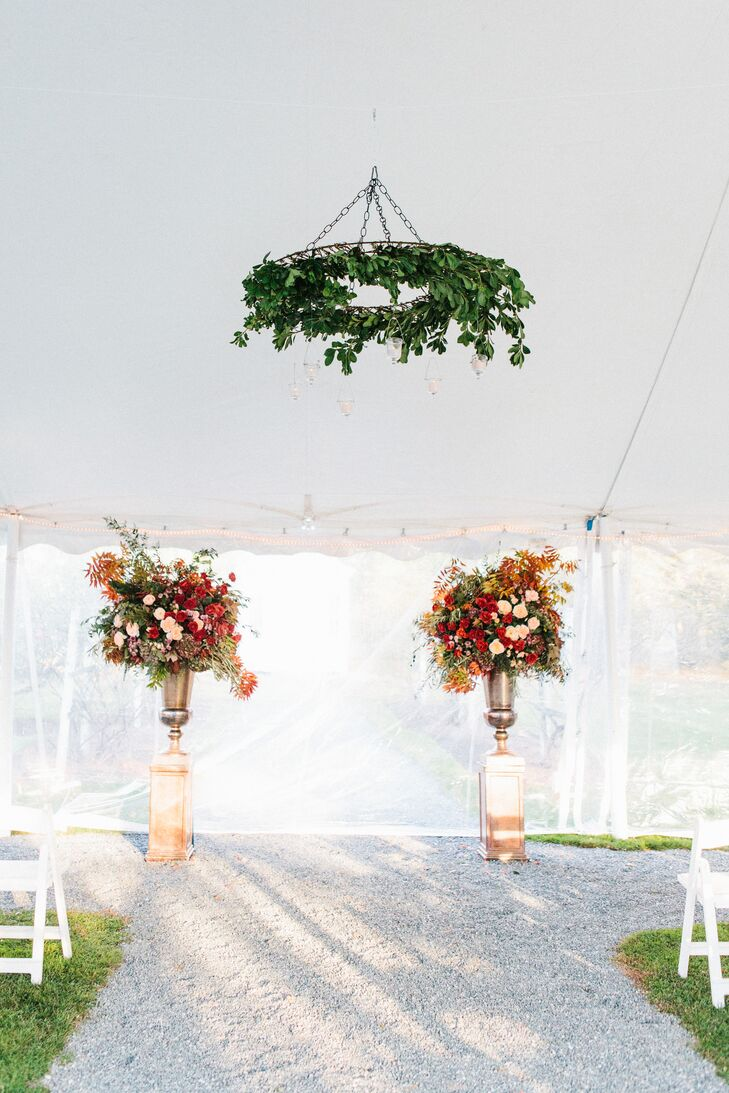 Rachel and John gave Semia of Flowers by Semia creative license over the wedding's florals, and she didn't disappoint. Oversize arrangements of roses, grasses, ferns, vines, amaranth, fall foliage, hydrangeas and more were arranged in stately silver urns, infusing the ceremony tent with a burst of bright, seasonal color. Above the spot where the couple exchanged vows, the talented florist suspended a garland of lush greenery and hanging candles, which created a focal point for the space.