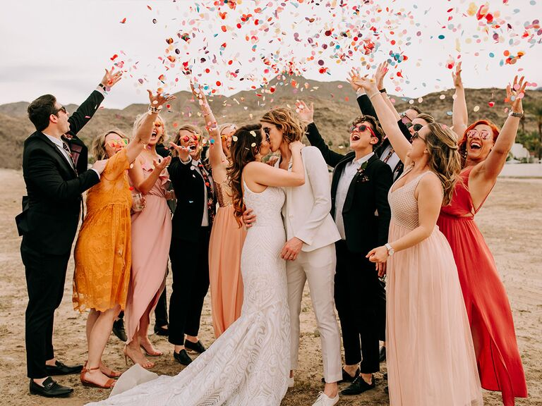 Couple celebrating with wedding party and confetti