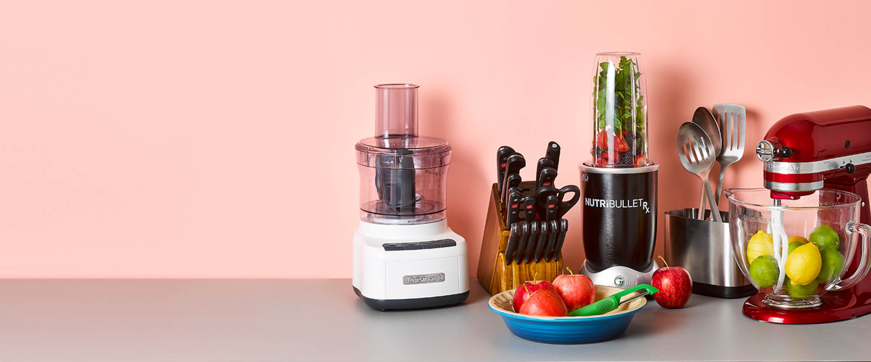Popular registry items arranged together including a Cuisinart food processor, Wüsthof knife set, Nutribullet blender, kitchen utensils, and a KitchenAid mixer.
